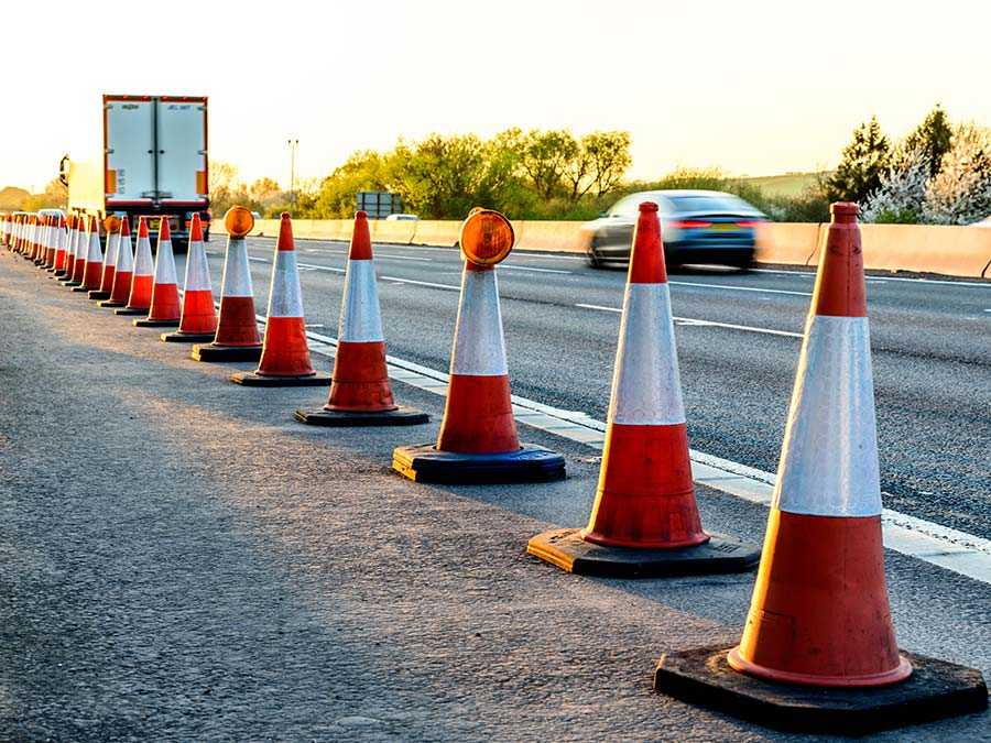 Multiple roadwork cones going along the edge of a motorway.